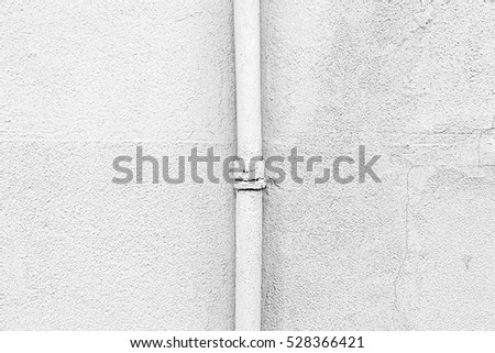 White wall with a pipe, detail of a textured wall