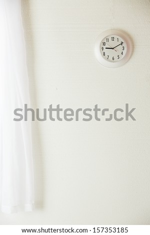 White wall with a white clock and a white curtain - stock photo