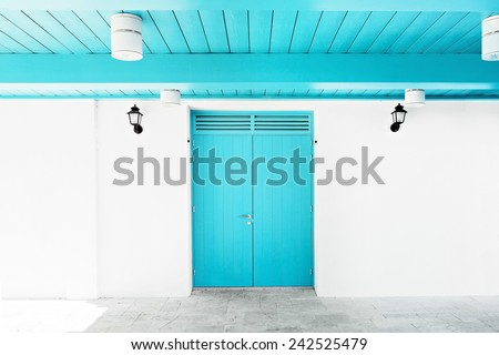 White wall with blue door and ceiling. Black lanterns at the entrance wall - stock photo