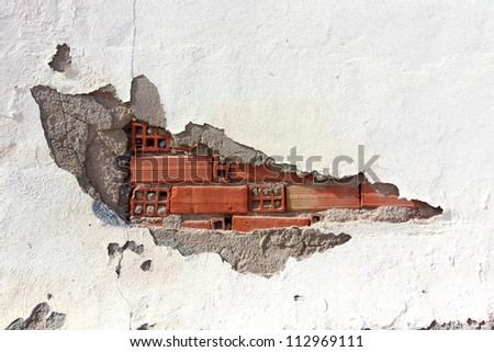 white wall with broken bricks and chipped being watched - stock photo