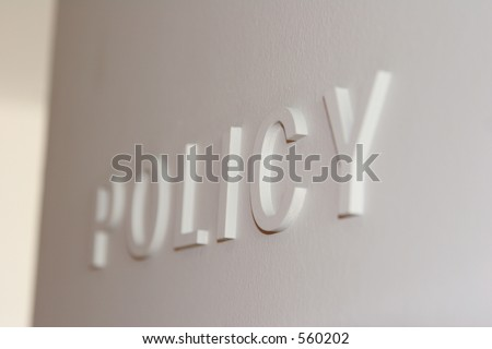 "White wall with the word ""policy"" embossed, partially blurred"