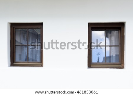 White wall with two old wooden stylized windows