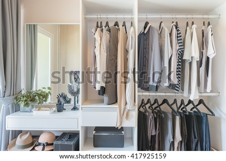 white wardrobe with shirts and pants hanging on rail - stock photo