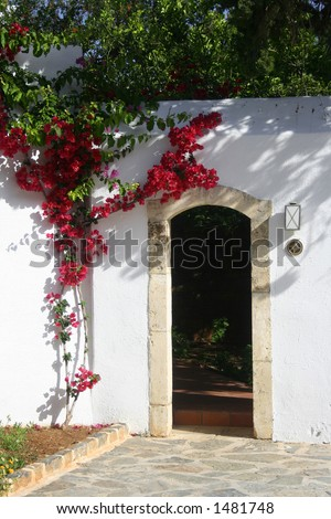 White wash stone house with arch door entrance and bougainvillea growing by the wall. - stock photo