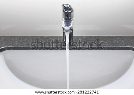 white washbasin and faucet on granite counter with water drop - stock photo