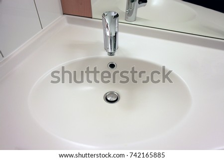 White Washbasin With Metal Tap In Bathroom Top View