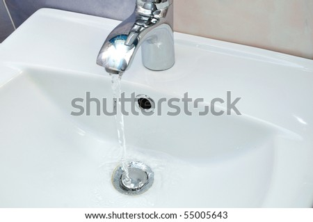 white washstand with flowing clean transparent water - stock photo