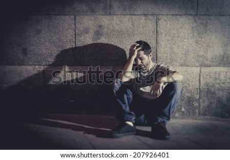 white wasted young man sitting on street ground with shadow on concrete wall feeling miserable and sad in urban scene representing depression and sickness - stock photo
