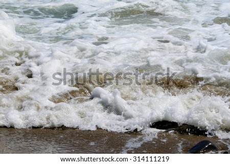 White water hitting the beach with small waves. - stock photo
