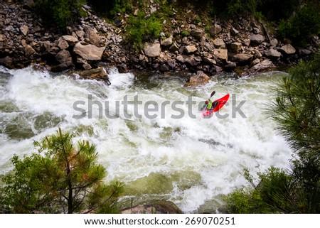 White Water Kayaker Riding River Rapids - stock photo