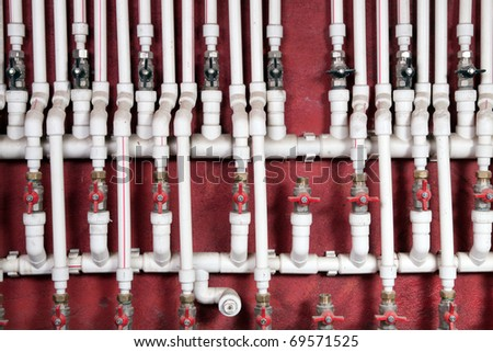 White water pipes against a red wall - stock photo