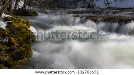 White water river flowing in the mountains in early spring - stock photo