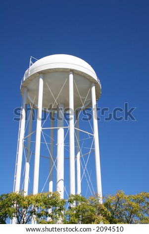 White water tower rising from trees against blue sky