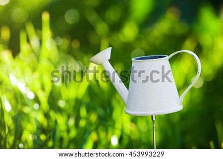 White watering can with green grass background, shallow DOF, outside - stock photo