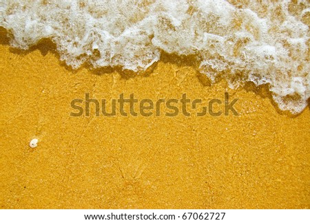 White wave on a sandy beach. - stock photo
