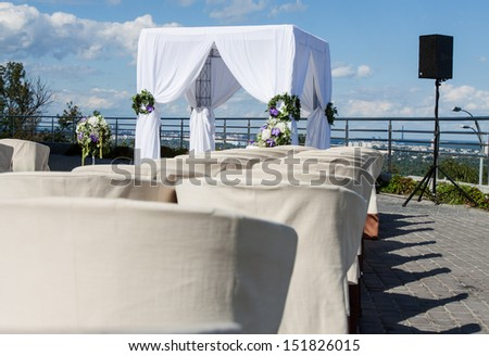 white wedding arch decorated with flowers outdoor - stock photo