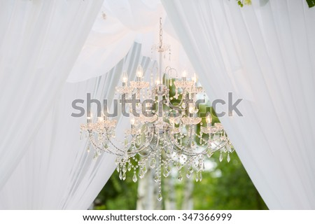 white wedding arch with a chandelier outdoors - stock photo