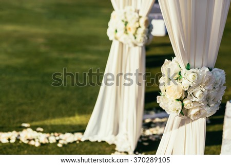 white wedding arch with flowers on sunny day in ceremony place with place for sign - stock photo
