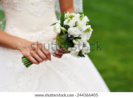white wedding bouquet in hands of the bride. - stock photo