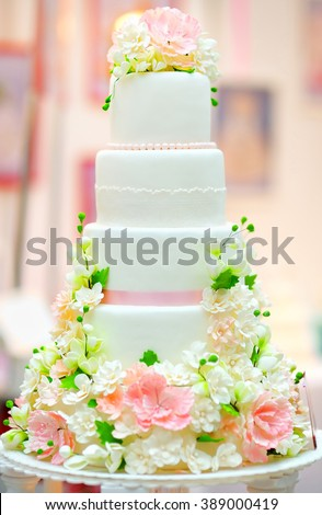 White wedding cake decorated with cream flowers - stock photo
