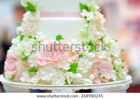 White wedding cake decorated with cream flowers close up - stock photo