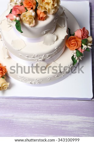 White wedding cake decorated with flowers on wooden table, close up