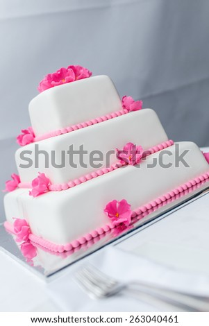 white Wedding Cake decorated with pink flowers - stock photo