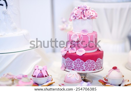 White wedding cake decorated with pink sugar flowers