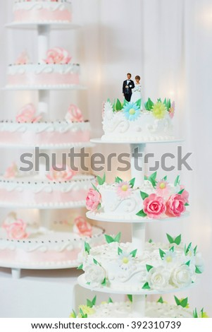 White wedding cake decorated with pink sugar flowers and bride and groom figurines on top - stock photo