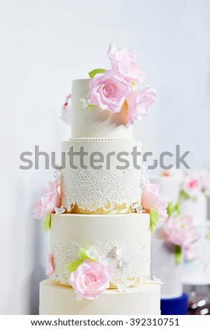 White wedding cake decorated with pink sugar peonies - stock photo