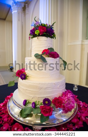 White wedding cake standing tall at a reception before guests get to enjoy dessert.