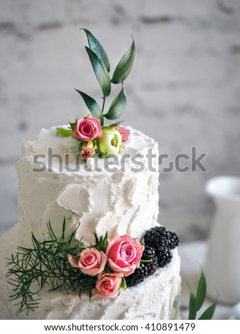 White wedding cake with flowers and blueberries - stock photo