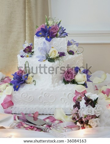White wedding cake with flowers at reception table - stock photo
