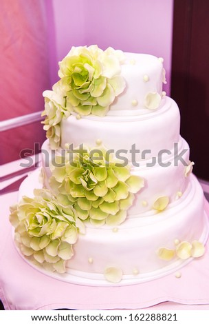 white wedding cake with green flowers - stock photo