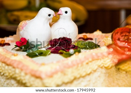 white wedding cake with two doves with rings decoration on top - stock photo