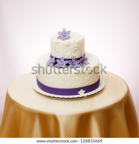 White wedding cake with violet marzipan flower decoration