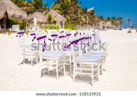 White wedding chairs decorated with purple bows on sandy beach - stock photo