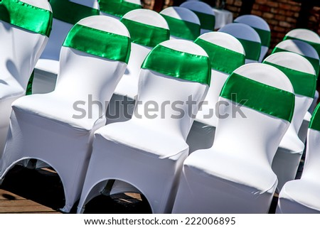 White wedding chairs with green ribbon outdoors  - stock photo
