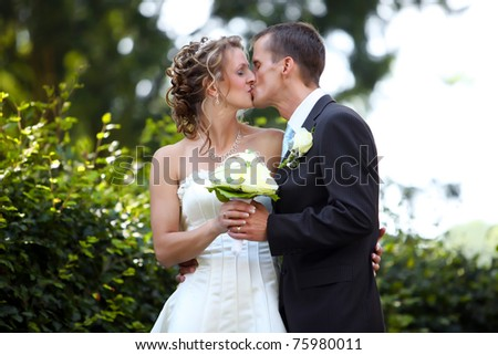 white wedding - Couple is kissing after marriage and holding flower bouquet - stock photo