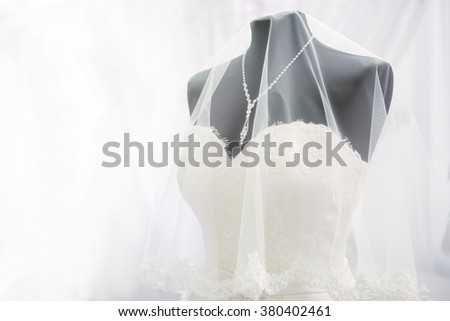 White wedding dress the bride on a black mannequin with necklace and veil on a white background. - stock photo