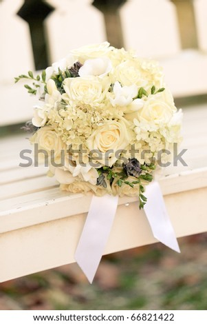 White wedding flowers on white wooden bench - stock photo