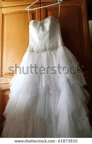 white wedding gown hanging from Cupboard door - stock photo