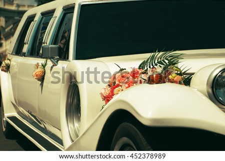 White wedding limousine decorated with flowers. - stock photo