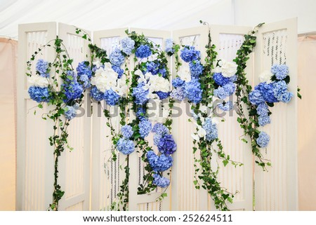 white wedding photo-booth with white and blue hydrangeas with green leaves - stock photo