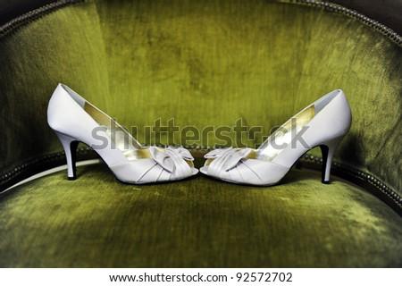 White wedding shoes on green velvet chair - stock photo