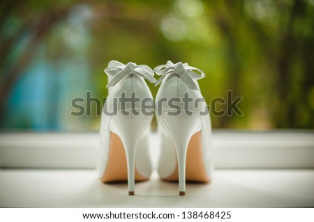 white wedding shoes with a bow on a heel on a green background - stock photo