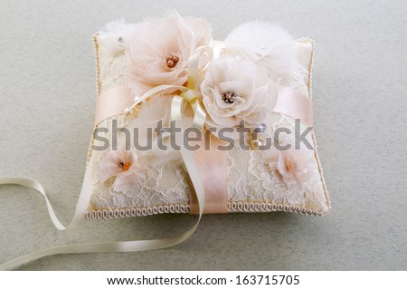 White wedding small satin pillow for rings on gray background  - stock photo
