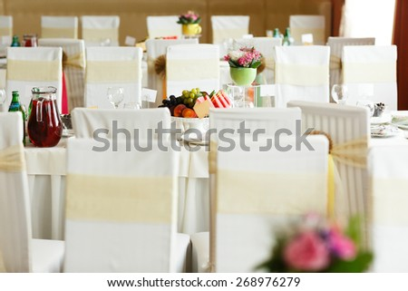 white wedding tables and chairs with fruits and decor  - stock photo