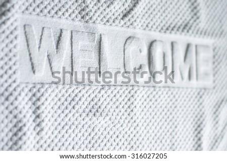 White welcome carpet mat shallow depth focus. - stock photo