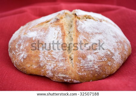 White wheat bread on red linen cloth - stock photo